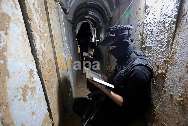 A Palestinian militant reads the Koran, Islam's holiest book at the tunnel in the east of Gaza city on the Muslim holy fasting month of Ramadan on May 24, 2018. Ramadan is sacred to Muslims because it is during that month that tradition says the Koran was revealed to the Prophet Mohammed. The fast is one of the five main religious obligations under Islam. More than 1.5 billion Muslims around the world will mark the month, during which believers abstain from eating, drinking, smoking and having sex from dawn until sunset. Photo by Ashraf Amra