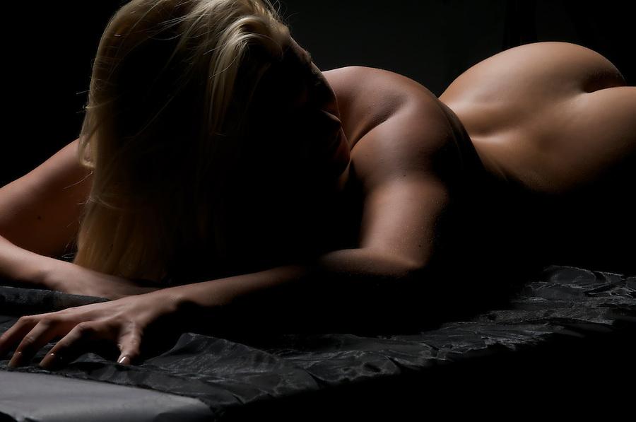 Youn caucasian blonde woman posing nude in dim light.