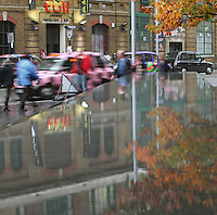 Fountain of More London reflecting the foliage of a tree and a Chinese restaurant in a street with multi-coloured London cabs, Greater London, UK. Picture by Manuel Cohen