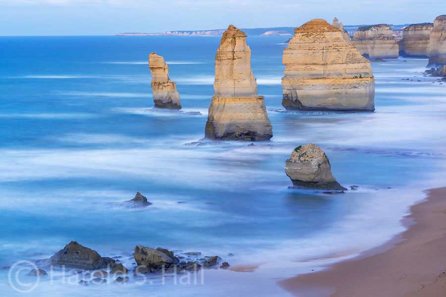 The Twelve Apostles is a collection of limestone stacks off the shore of the Port Campbell National Park, by the Great Ocean Road in Victoria, Australia.  The pile of rocks in the foreground is an eroded, fallen apostle.  Surprisingly this is a free attraction.