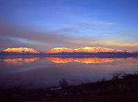Scenic landscape of Mount Timpanogos reflected in Utah Lake under a wide sky at dusk. Rocky Mountains, Utah.