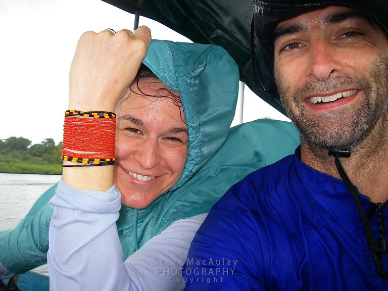Smiling couple soaked by rain storm on small baot, Bocas Del Toro, Panama