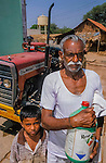 An Indian farmer and son .    Round up is widely used in Karnataka state.  A  Monsanto product which is sold in conjunction  with round up resistent  crops.