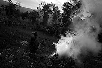 A woman burns dried grass in the infamous village of Kaniola, known for its regular massacres in the Eastern DRC province of South Kivu on Thursday May the 8th 2008.///.On thursday night fighting between the congolese army ( FARDC ) and militias left one man dead and 10 severally wounded...In Eastern DRC rape can be used as a weapon to undermine the whole social structure. Sexual violence is often used to weaken any opposition in the population. .Many women have been so sadistically attacked from the inside out, butchered by bayonets and assaulted with chunks of wood, that their reproductive and digestive systems are beyond repair. .According to the United Nations, 27,000 sexual assaults were reported in 2006 in South Kivu Province alone, and that may be just a fraction of the total number across the country. ?The sexual violence in Congo is the worst in the world,? said John Holmes, the United Nations under secretary general for humanitarian affairs..The attacks go on despite the presence of the largest United Nations peacekeeping force in the world, with more than 17,000 troops. ..NAMES AND AGE OF THE SUBJECTS HAVE BEEN OMITTED TO PROTECT THEIR IDENTITIES.
