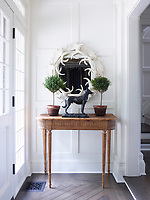 In the entrance hall the console is 19th-century French oak, the antique bronze dog is by Christophe Fratin, the moose antler mirror is vintage, and the walls are painted in Benjamin Moore's Mascarpone.