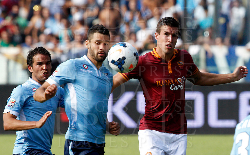 Calcio, Serie A: Roma vs Lazio. Roma, stadio Olimpico, 22 settembre 2013.<br /> From left, Lazio midfielders Alvaro Gonzalez, of Uruguay, Antonio Candreva and AS Roma midfielder Kevin Strootman, of the Netherlands, fight for the ball during the Italian Serie A football match between AS Roma and Lazio, at Rome's Olympic stadium, 22 September 2013.<br /> UPDATE IMAGES PRESS/Riccardo De Luca