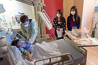 "Occidental College pre-med students Elizabeth Cortez-Toledo '14 (polka dot top) and Karina Ortiz '15 (black sweater, purple top) observe Dr. Kyle McCallin examining a patient in the pulmonary isolation unit at Children's Hospital Los Angeles, Jan. 18, 2013. They also shadowed Dr. Cheryl Lew, attending physician in the pulmonology department.<br /> Made possible by the Occidental College Office of Pre-Health Advising (OPHA) in the Hameetman Career Center, 10 Oxy pre-meds spent the last two weeks of their winter break ""shadowing"" doctors at Children's Hospital Los Angeles, a teaching hospital run by USC's Keck School of Medicine, to get a better sense of what the practice of medicine entails. Their packed 10 days, which began as early as 7:30 a.m., included rotations in 10 different areas: general pediatrics, cardiology, genetics, rehabilitation, pulmonology, gastroenterology, plastic surgery, rheumatology, hematology and dentistry. Teams of two observed surgeries and accompanied physicians on their clinical rounds in a different department each day.<br /> (Photo by Marc Campos, Occidental College Photographer)"