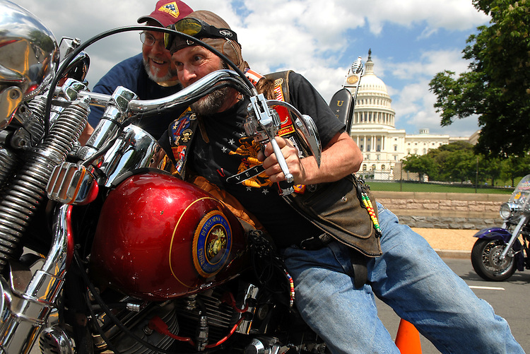 "Jerry Sonnier, right, of the Patriotic Guard pushes his bike into position before a news conference to applaud the ""Respect for America's Fallen Heroes Act,"" which protects funerals services of fallen service men and women from protesters.  The Patriotic Guard attends funerals as invited guests and shields family and friends from interruptions created by protesters.  They do this in a legal and non-violent fashion."