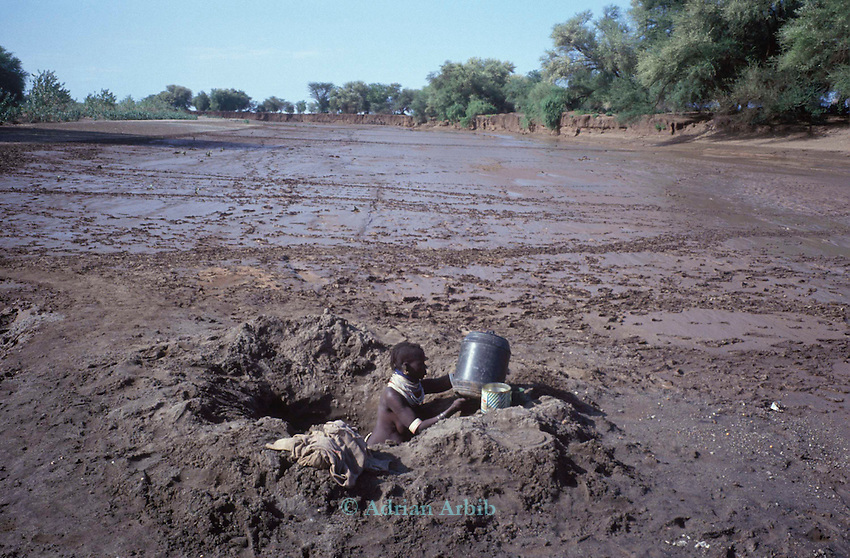 A Turkana woman collects  water from a  nearby ground source to her  village...Northern Kenya.....