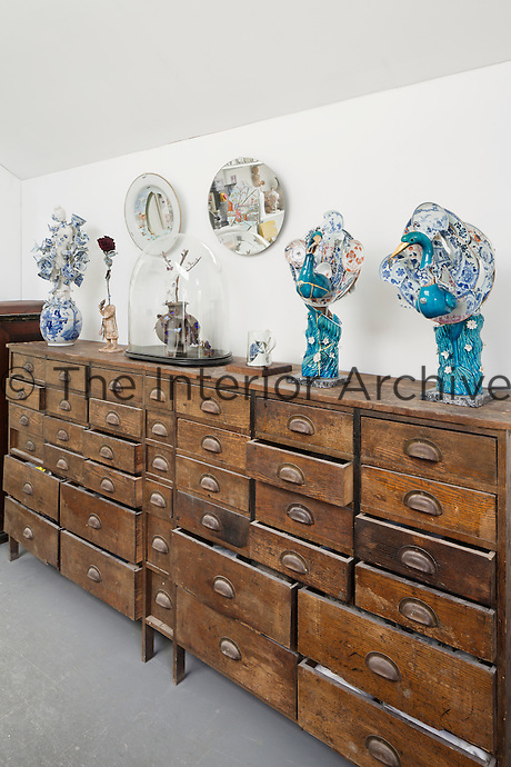 In the studio, an antique chest of drawers displays a pair of cobalt peacocks made from fragments of Chinese porcelain with gold plated beaks, a Han dynasty cocoon jar, a Tang dynasty figure and porcelain flowers made from Chinese tea bowls.