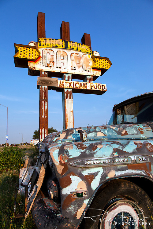 A late 50's Chevrolet Apache pickup truck stands next to the weather worn sign for the Ranch House Cafe along Route 66 in Tucumcari, New Mexico.