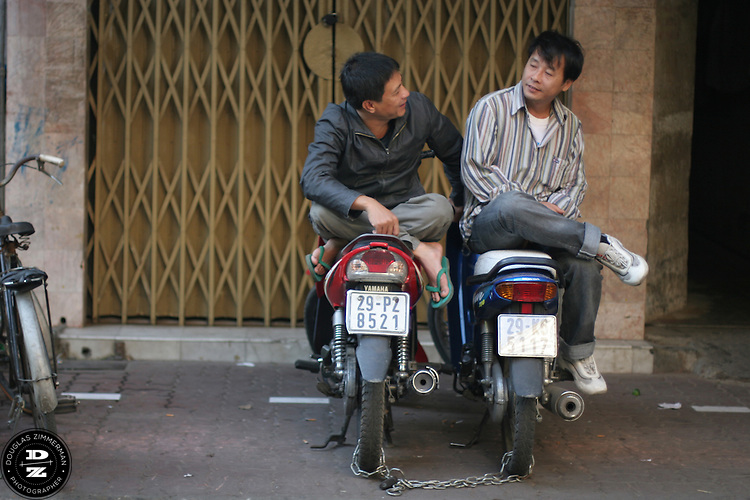 Two men share a conversation while resting on motorbikes on a sidewalk in the Old Quarter of Hanoi, Vietnam.  Photograph by Douglas ZImmerman