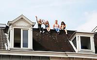 Nederland  Cuijk  2016. De Vierdaagse van Nijmegen. Meisjes bekijken vanaf een dak de wandelaars op de Via Gladiola.  Foto Berlinda van Dam / Hollandse Hoogte