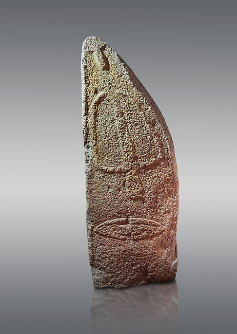 Late European Neolithic prehistoric Menhir standing stone with carvings on its face side. The representation of a stylalised male figure starts at the top with a long nose from which 2 eyebrows arch around the top of the stone. below this is a carving of a falling figure with head at the bottom and 2 curved arms encircling a body above. at the bottom is a carving of a dagger running horizontally across the menhir. Excavated from Pranu Maore I site,  Laconi. Menhir Museum, Museo della Statuaria Prehistorica in Sardegna, Museum of Prehoistoric Sardinian Statues, Palazzo Aymerich, Laconi, Sardinia, Italy. Grey background.