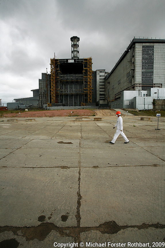 "Chernobyl plant worker Sergei Koshelev crosses the high-radiation zone beside Chernobyl's ground zero. The concrete and lead Sarcophagus encloses the ruins of the reactor hall where the meltdown occurred. The Sarcophagus leaks and is structurally unstable. Construction workers preparing foundations for a replacement ""New Safe Confinement"" can hit their maximum daily dose in two to three hours.  <br /> ------------------- <br /> This photograph is part of Michael Forster Rothbart's After Chernobyl documentary photography project.<br /> © Michael Forster Rothbart 2007-2010.<br /> www.afterchernobyl.com<br /> www.mfrphoto.com <br /> 607-267-4893 o 607-432-5984<br /> 5 Draper St, Oneonta, NY 13820<br /> 86 Three Mile Pond Rd, Vassalboro, ME 04989<br /> info@mfrphoto.com<br /> Photo by: Michael Forster Rothbart<br /> Date: 7/2009    File#:  Canon 5D digital camera frame 72232<br /> ------------------- <br /> Original caption: .Sergei Koshelev, videographer for the Chernobyl SIP PMU (Shelter Implementation Plan Project Management Unit) visits the high-radiation zone just west of the Chernobyl Nuclear Power Plant's 4th Block Shelter (also called the Sarcophagus). Workers refer to the area inside the final high-security perimeter as the ""local zone,"" where they are doing groundwork for construction of the New Safe Confinement super-structure that will replace the Sarcophagus.."