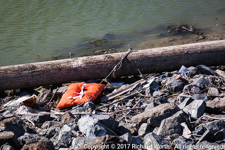 A life vest lies abandoned on the rocky shore at the San Leandro Marina on San Francisco Bay.
