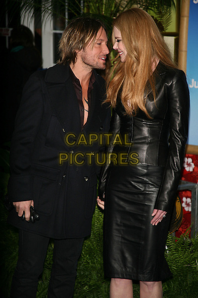 """KEITH URBAN & NICOLE KIDMAN.The New York Premiere of """"Just Go With It"""" at the Ziegfeld Theater, New York, NY, USA..February 8th, 2011.half length black leather pink beige pussybow blouse jacket skirt holding hands married husband wife tall short trench coat jeans profile tall short.CAP/LNC/TOM.©TOM/LNC/Capital Pictures."""
