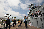 Volunteers with the Pacific Battleship Center reel in the chains for the final voyage of the battleship USS Iowa from Berth 51 to its new home at Berth 87 in San Pedro, Los Angeles, CA where it opens as a museum ship in July 2012.