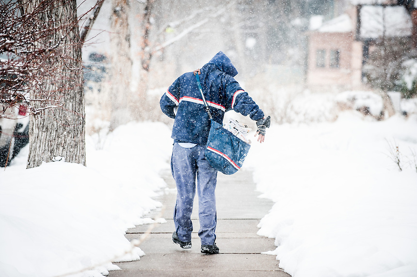 A walking mailman delivers letters to residences on a residential street as snow falls in Denver, Colorado on February 26, 2013.