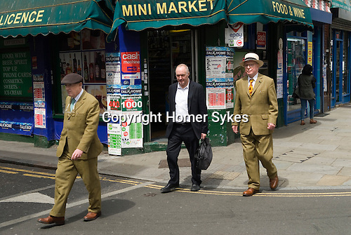 Gilbert and George who are artists walking down Brick Lane London E1.