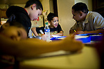 Dennis Sawyer, right, helps his son Daniel, center, with his homework January 27, 2010 in Sacramento, Calif. The Sawyer family receives $540/month in CalWORKs assistance from the state of California. Dennis is currently unable to work while recovering from cancer, and Sophia hasn't been able to find work. Gov. Arnold Schwarzenegger has proposed eliminating the CalWORKs program in an effort to balance the state's budget. CREDIT: Max Whittaker for The Wall Street Journal.CABUDGET