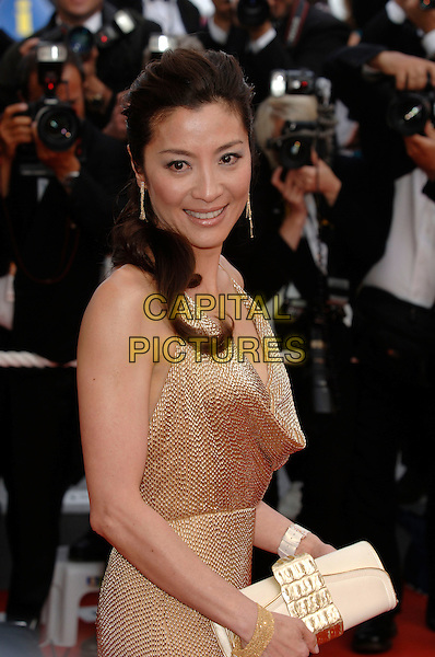 """MICHELLE YEOH.""""Over the Hedge"""" screening arrivals.59th International Cannes Film Festival, France.21st May 2006.Ref: PL.half length gold dress pink clutch purse.www.capitalpictures.com.sales@capitalpictures.com.©Phil Loftus/Capital Pictures"""