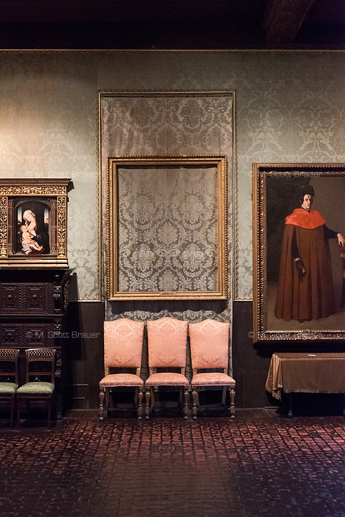 """An empty frame hangs on the wall where Rembrandt's """"The Storm on the Sea of Galilee"""" once hung in the Isabella Stewart Gardner Museum's """"Dutch Room,"""" in Boston, Mass., USA, seen here on Tues., Dec. 5, 2017. The painting was stolen during a 1990 theft of 13 objects from the museum: 10 paintings, 2 objects, and 1 etching. One of the objects stolen was a Shang Dynasty ku (or gu), a bronze beaker, which stood on the table at right under the painting of the man in red, Zurburan's painting """"A Doctor of Law,"""" at right."""