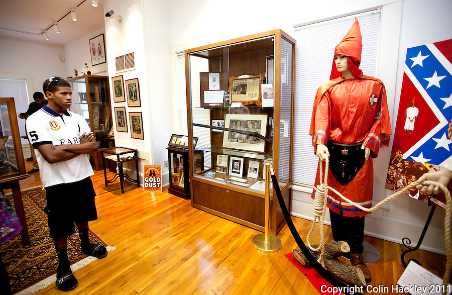 CONFRONTING HISTORY: Chris Blackwell, age 17 of Mansfield, Texas, looks at the Ku Klux Klan robe displayed in the The Black Archives Komics, Koon and Klan (KKK) Collection in Tallahassee. .COLIN HACKLEY PHOTO