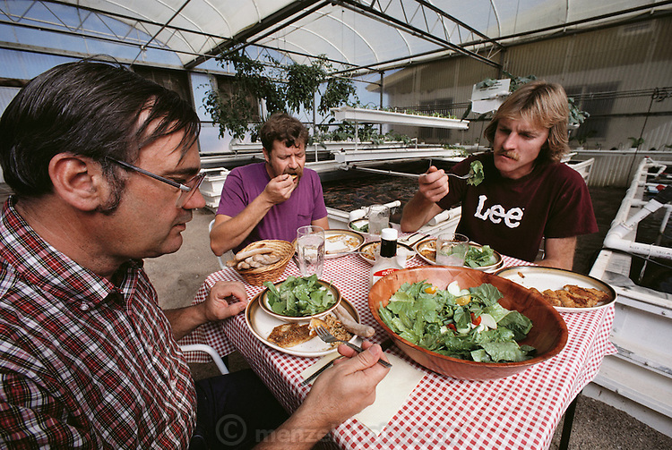 USA_SCI_BIOSPH_71_xs <br /> Biosphere 2 Project environmental research lab. Eating lunch of tilapia fish harvested from the Bioshphere 2 rice fields during a test phase prior to the sealing of the Biosphere.  Biosphere 2 was a privately funded experiment, designed to investigate the way in which humans interact with a small self-sufficient ecological environment, and to look at possibilities for future planetary colonization. The $30 million Biosphere covers 2.5 acres near Tucson, Arizona, and was entirely self- contained. The eight &lsquo;Biospherian&rsquo;s&rsquo; shared their air- and water-tight world with 3,800 species of plant and animal life. The project had problems with oxygen levels and food supply, and has been criticized over its scientific validity. 1987