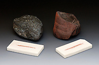 Specular black hematite (left) and a dark red form of hematite (right), both showing their respective diagnostic rust-red streak. Hematite, the primary ore of iron, ranges from red to black, but a streak test will always reveal the same hue of red. Streak plates are unglazed white porcelain tiles.