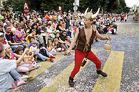 Switzerland. Canton of Neuchâtel. Neuchâtel. Grape Harvest Festival. A man, dressed up as Astérix the famous hero from the comic strip, holds a sword and an empty bottle of wine. He plays wth the children in the Public during the parade. Confettis on the road. Pedestrian crossing. © 2006 Didier Ruef