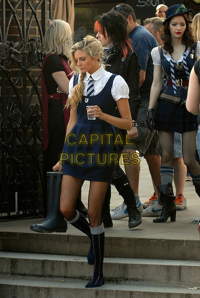 "TAMSIN EGERTON.Filming on the set of ""St Trinian's: The Legend of Fritton's Gold"", outside the Globe Theatre, London, England..August 10th, 2009.2 full length blue dress black boots white shirt steps cup water drink beverage side view film movie .CAP/IA.©Ian Allis/Capital Pictures."