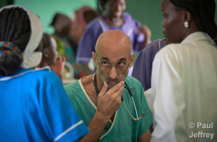 "Dr. Tom Catena, a Catholic lay missionary from the United States, listens to a nurse during rounds in the Mother of Mercy Hospital in Gidel, a village in the Nuba Mountains of Sudan. The area is controlled by the Sudan People's Liberation Movement-North, and frequently attacked by the military of Sudan. The Catholic hospital, at which Catena is often the only physician, is the only referral hospital in the war-torn area. Catena is popularly referred to as ""Doctor Tom""."