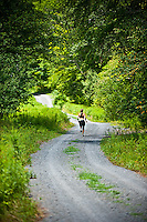 Female athlete running down gravel road