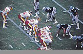 Washington Redskins quarterback Jay Schroeder (10) examines the <br /> Los Angeles Raiders defense as he calls signals during their game at RFK Stadium in Washington, D.C. on September 14, 1986.  The Redskins won the game 10 - 6.  Redskins players pictured in addition to Schroeder are: tight end Don Warren (85), left tackle Joe Jacoby (66), left guard Russ Grimm (68), center Jeff Bostic (53), right guard R.C. Thielemann (69), right tackle Mark May (73), and wide receiver Art Monk (81). Los Angeles Raiders players pictured include: right defensive end Sean Jones (99), nose tackle Bill Pickel (71), and left inside linebacker Matt Millen (55).<br /> Credit: Arnold Sachs / CNP
