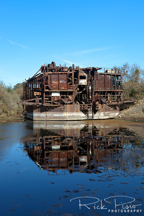 Constructed in 1933 at a cost of $543,148 the Tuolumne Gold Dredge has sat idle since 1951. Located near the former mining town of La Grange, in California's Gold Country, the dredge weighed over 2500 tons and floated on its own self-created pond of water. The dredge's boom consisted of 120 buckets weighing 4000 pounds each that extended 70 feet below the waters surface. The total amound of gold recovered by the dredge is not known. The dredge is registered as historic landmark #1971000208.
