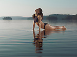 Young woman practicing Hatha yoga on a platform in water on the lake in the morning. Yoga Upward Facing Dog, Cobra variation posture, Urdhva Mukha Svanasana. Also Pilates Swan posture. Muskoka, Ontario, Canada.