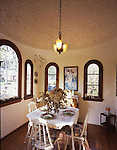 The breakfast room, the owner's favorite room, has a unique roughly patterned plaster ceiling. The art-glass chandelier is original to the house.
