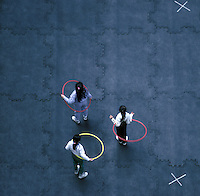 3 girls with hoola-hoops on rooftop playground