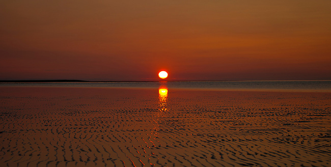 The sun rises over a tidal flat on Cook Inlet in Lake Clark National Park, Alaska. Photo by Gus Curtis.