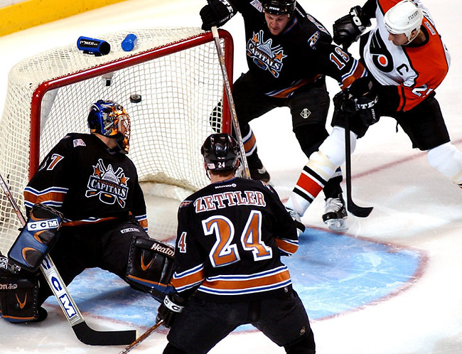 Philadelphia Flyers' Keith Primeau, right, scores a goal in the first 30 seconds of the game beating Washington Capitals goalie Olie Kolzig (37) in Philadelhia Thursday Nov.15, 2001.  Washington Capitals center Andrei Nikolishin (13) and defenseman Rob Zetter (24) look on.(AP Photo/Brad C Bower)