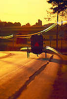 Amish carriage driving down a road at sunset. Strasburg Pennsylvania USA Lancaster County.