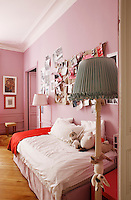 The traditional 19th century panelling in this girl's room has been painted a contemporary powdery rose pink and the framed painting on the far wall is by Linde Bialas