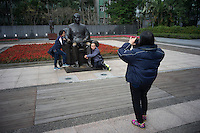 Hong Kong tourists pose for pictures with a bronze statue of the Father of Modern China, Dr. Sun Yat-sen at the National Dr. Sun Yat-sen Memorial Hall in Taipei, Taiwan, 2015.