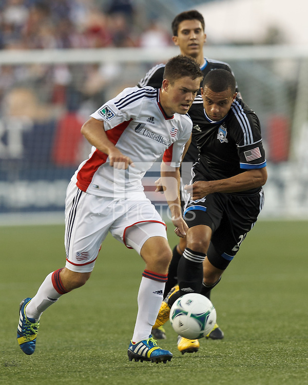 New England Revolution midfielder Kelyn Rowe (11) on the attack as San Jose Earthquakes defender Jason Hernandez (21) defends. In a Major League Soccer (MLS) match, the New England Revolution (white) defeated San Jose Earthquakes (black), 2-0, at Gillette Stadium on July 6, 2013.