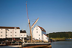 Historic sailing barge and whitewashed buildings of the Tide Mill on the River Deben, Woodbridge, Suffolk, England, UK