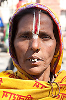 Kathmandu, Nepal.  A Hindu Woman in Durbar Square.  She wears a tilak on her forehead, indicating that she is a devotee of Lord Vishnu and his incarnations.  She also wears a jewelry pin in her left nostril, and suffers from bad teeth.