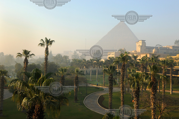 The Giant Pyramid of Cheops rising behind the landscaped gardens of the five star Mena House Hotel. A former nineteenth century hunting lodge, and a Cairo institution, it is now owned by the Oberoi group of luxury hotels.