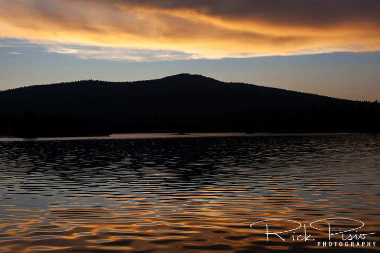 The waters of Butte Lake reflect the sunset with the silhoutte of Prospect Peak in the background. Prospect Peak sits atop a shield volcano to the northwest of Butte Lake in Lassen Volcanic National Park.