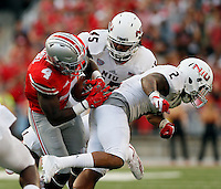 Ohio State Buckeyes running back Curtis Samuel (4) fumbles the ball after being hit by Northern Illinois Huskies linebacker Boomer Mays (45) and safety Marlon Moore (2) during the fourth quarter of the NCAA football game at Ohio Stadium in Columbus on Sept. 19, 2015. (Adam Cairns / The Columbus Dispatch)